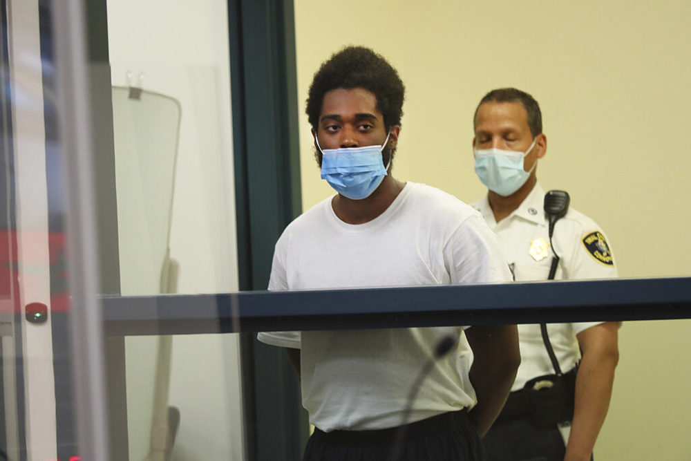 Jamhal Latimer, left, one of 11 people charged in connection with an armed standoff along I-95 last weekend, appears during his arraignment at Malden District Court on Tuesday.  (Suzanne Kreiter/The Boston Globe via AP, Pool)