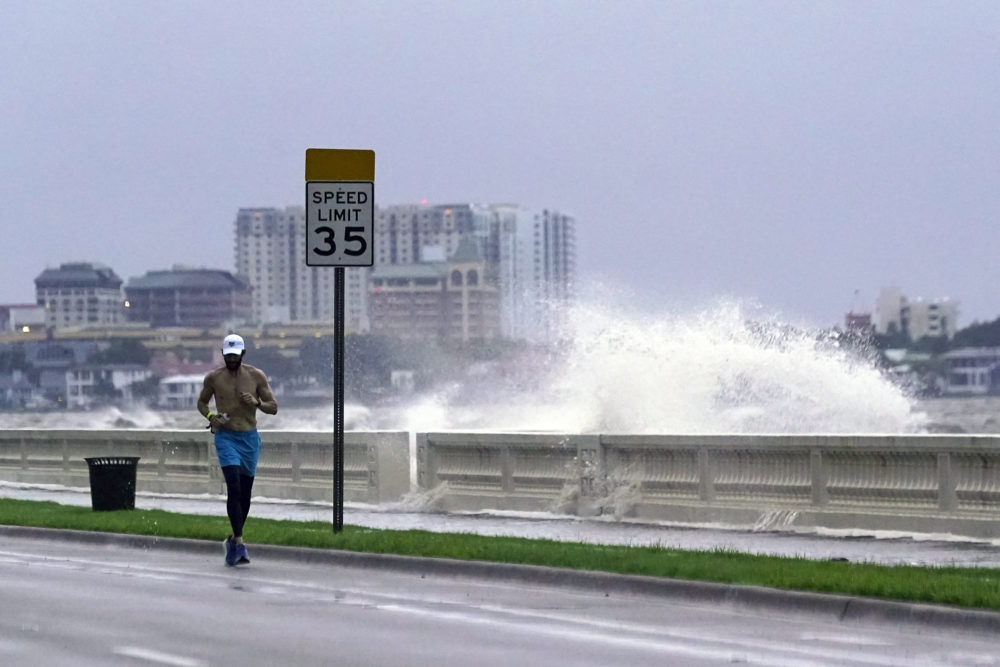 A jogger makes his way in Tampa, Fla. as a wave breaks over a seawall, during the aftermath of Tropical Storm Elsa Wednesday, July 7, 2021. The Tampa Bay area was spared major damage as Elsa stayed off shore as it passed by. (John Raoux/AP)