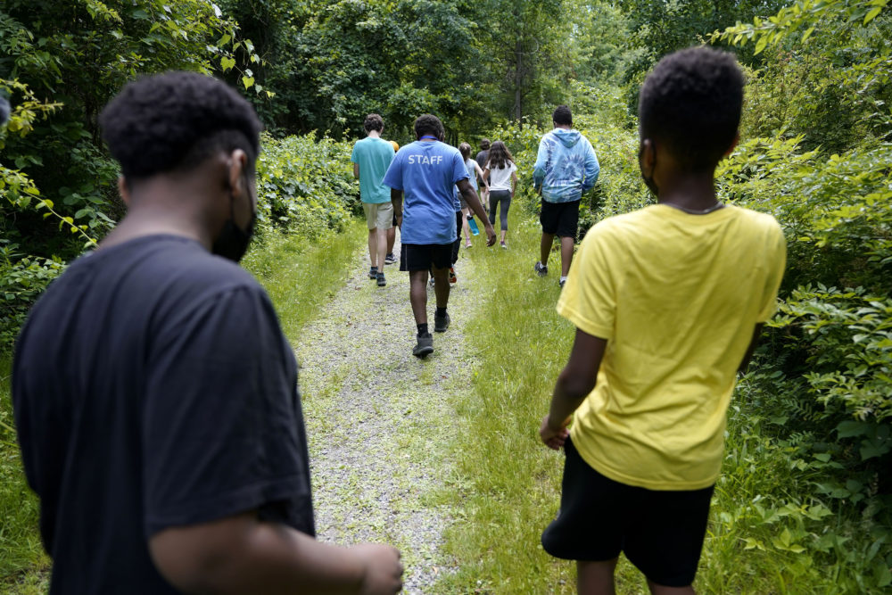 Students Giovanni Pierre, foreground left, and Aaron Overton, foreground right, walk behind camp educator Jamil Boykin, center, during a hike at Mass Audubon's Boston Nature Center and Wildlife Sanctuary, in Mattapan. (Steve Senne/AP)