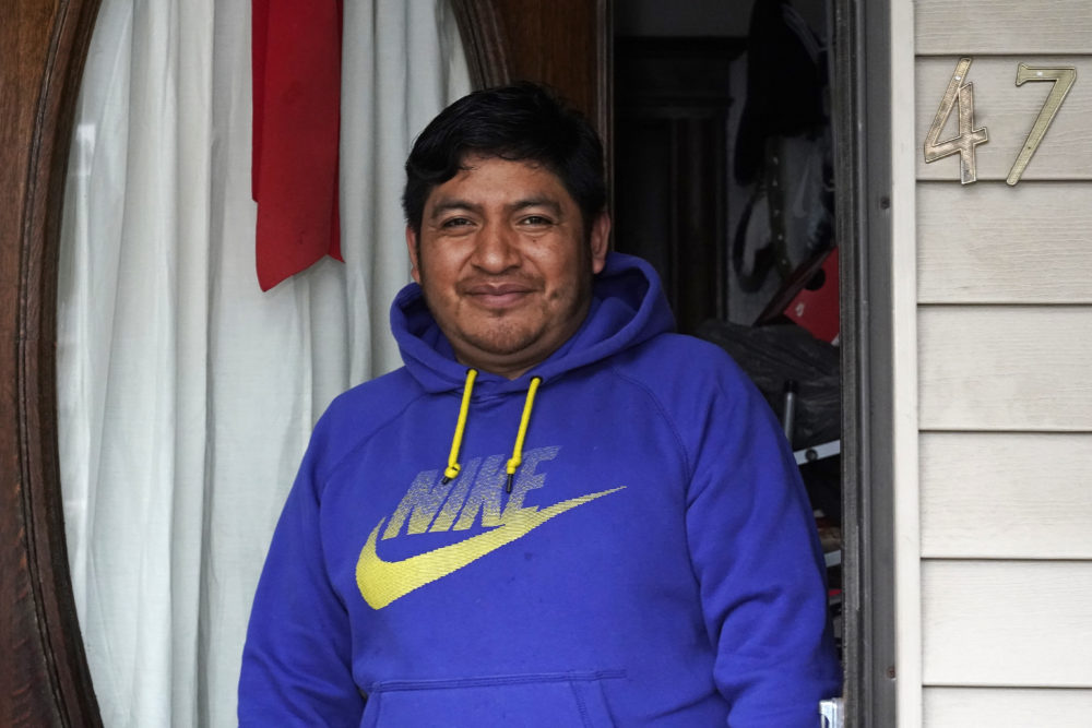 Lucio Perez poses in the front doorway of his home, where he has lived with his family since March, July 8, 2021, in Springfield. Just a few months ago, Perez moved out of a western Massachusetts church he'd lived in for more than three years to avoid deportation. (Charles Krupa/AP)
