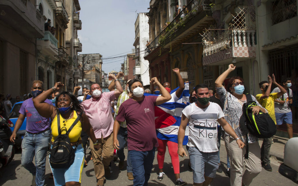Government supporters shout slogans as anti-government protesters march in Havana, Cuba. Hundreds of demonstrators went out to the streets in several cities in Cuba to protest against ongoing food shortages and high prices of foodstuffs. (Ismael Francisco/AP Photo)