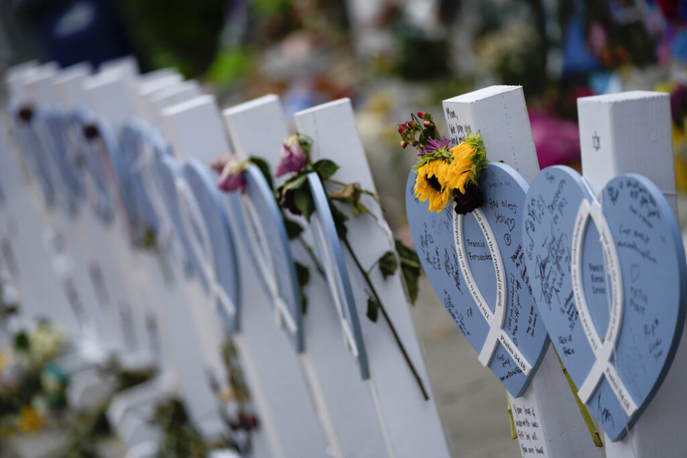 Flowers and messages of love adorn wooden hearts with the names of victims of the Champlain Towers South building collapse, at a makeshift memorial near the site, on Monday, July 12, 2021, in Surfside, Fla.(AP Photo/Rebecca Blackwell)