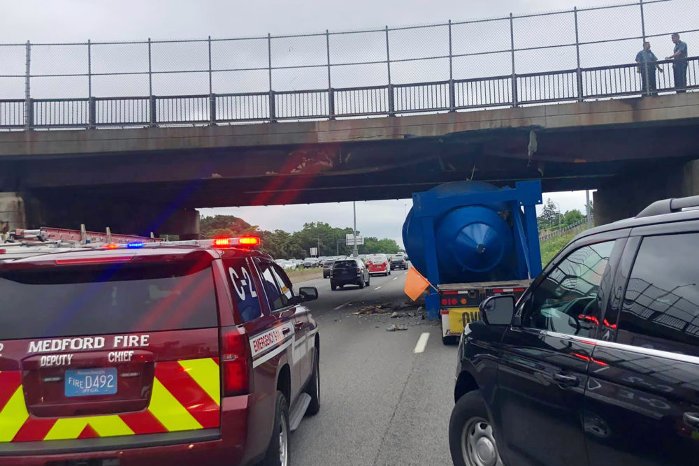 A crew works at the scene of the Roosevelt Circle overpass on I-93 southbound in Medford, Mass., Monday, July 19, 2021, which was extensively damaged after it was hit by an oversized tractor-trailer hauling a large metal structure. (Medford Fire Department via AP)