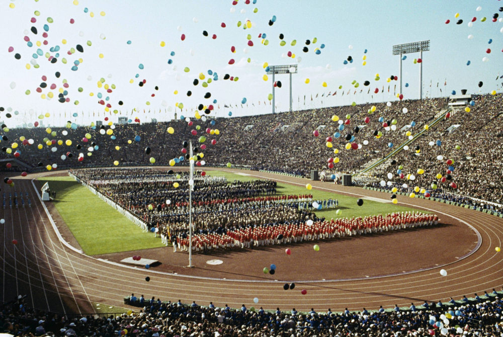 On this Oct. 10, 1964, file photo, balloons fly over Olympians and spectators during the opening ceremony of the 1964 Summer Olympics at the National Stadium in Tokyo. The famous 1964 Tokyo Olympics highlighted Japan's resiliency. It was a prospering country that was showing off bullet trains, transistor radios, and a restored reputation just 19 years after devastating defeat in World War II. (AP)