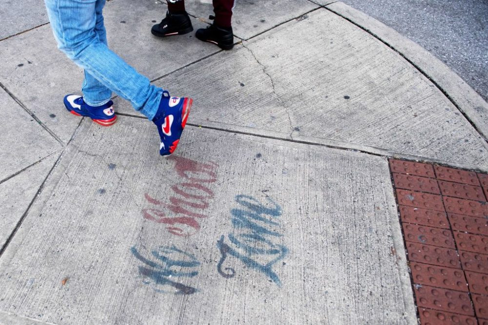 """Two men walk past a sign spray painted on the sidewalk stating """"No Shoot Zone"""" in Baltimore, Maryland, on Dec. 17, 2018. (Jim Watson/AFP/Getty Images)"""