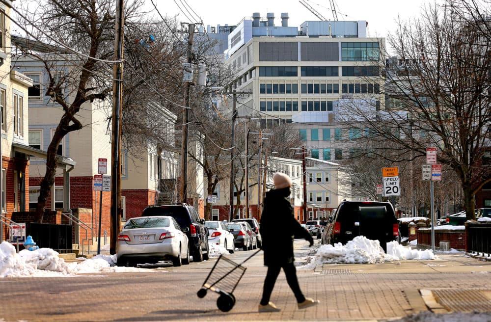 A woman walks by the Washington Elms Housing Development as high rise towers rise in Kendall Square nearby in Cambridge, MA  on Feb. 13, 2021. (John Tlumacki/The Boston Globe via Getty Images)