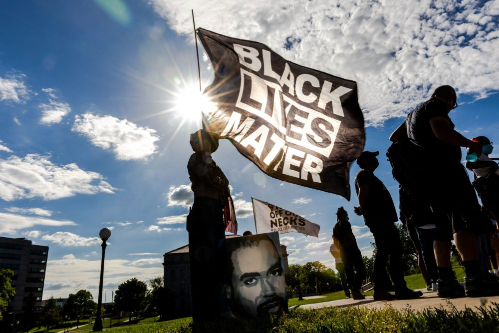 A woman holds a Black Lives Matter flag during an event in remembrance of George Floyd outside the Minnesota State Capitol on May 24, 2021. (Kerem Yucel/AFP via Getty Images)