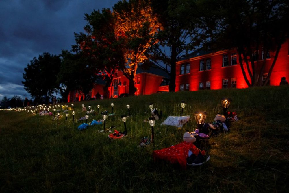 Shoes, flowers, and stuffed animals sit outside the former Kamloops Indian Residential School where flowers and cards have been left as part of a growing makeshift memorial to honour the 215 children whose remains have been discovered buried near the facility in Kamloops on June 5, 2021. (Photo by Cole Burston / AFP) (Photo by COLE BURSTON/AFP via Getty Images)