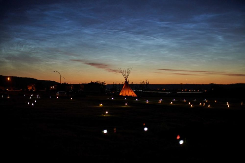 Solar lights and flags mark the spots where 751 human remains were recently discovered in unmarked graves at the site of the former Marieval Indian Residential School on the Cowessess First Nation in Saskatchewan on June 27, 2021. (Geoff Robins/AFP/Getty Images)
