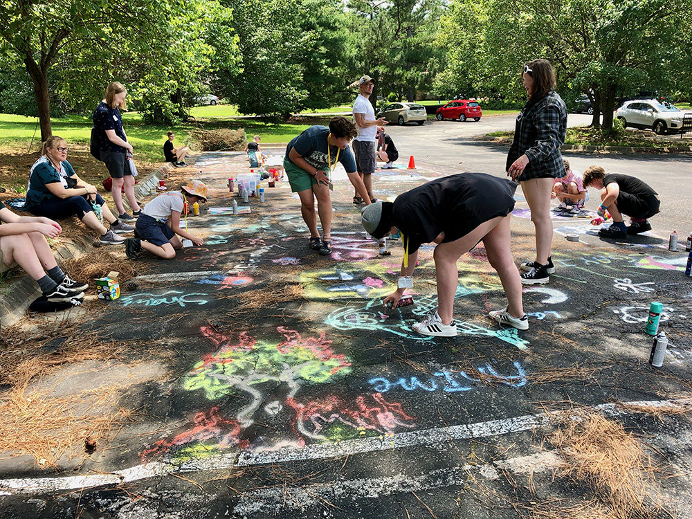 Queer camp youth ages 12 to 18 spray paint and glitter artworks on the parking lot of Good Shepherd Lutheran Church as parents and a camp counselor observe on July 6, 2021, in Fayetteville, Arkansas. (Jacqueline Froelich/KUAF)
