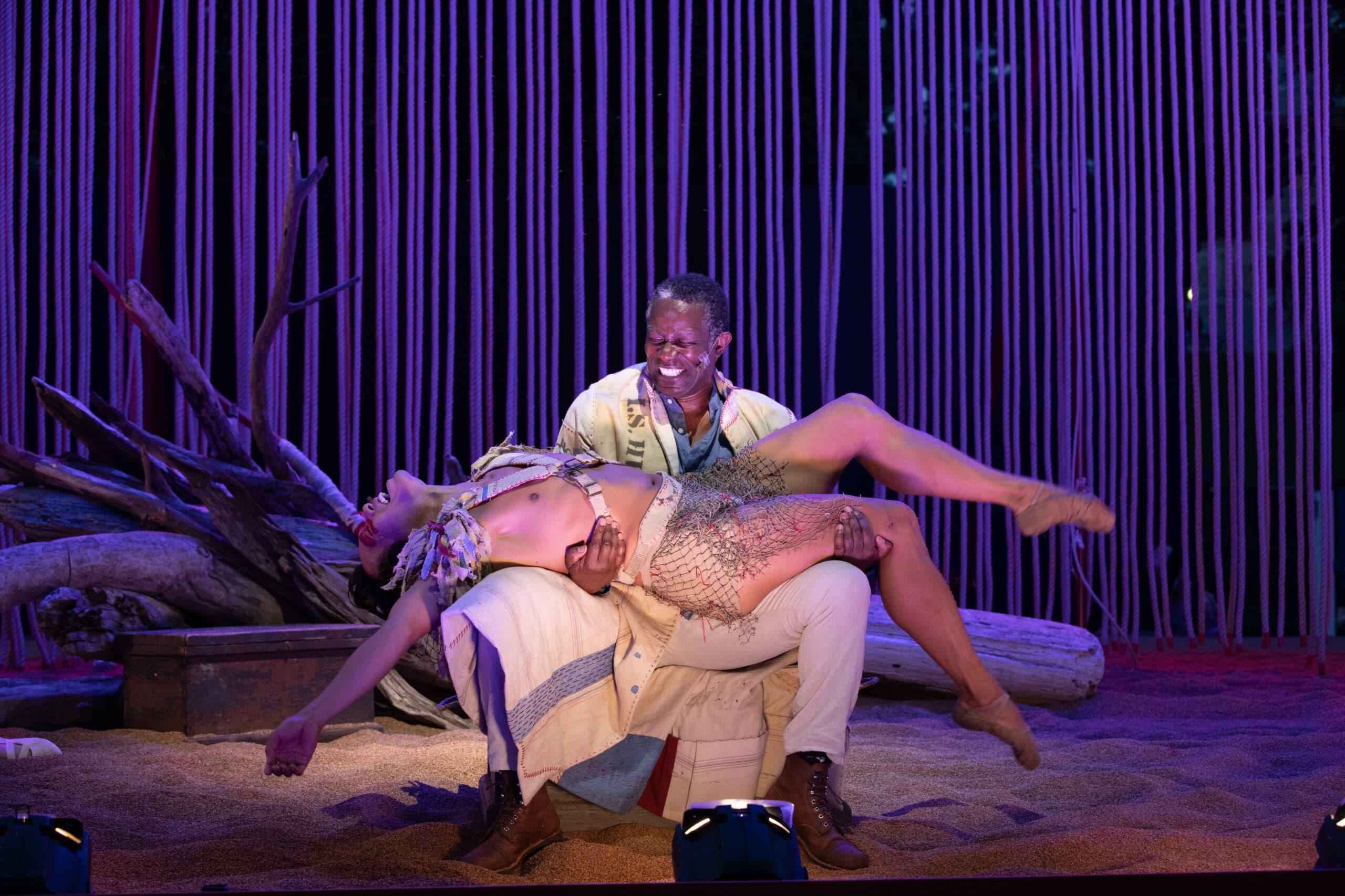 "John Douglas Thompson as Prospero cradles John Lam's Ariel in ""The Tempest"" on Boston Common. (Courtesy Evgenia Eliseeva)"