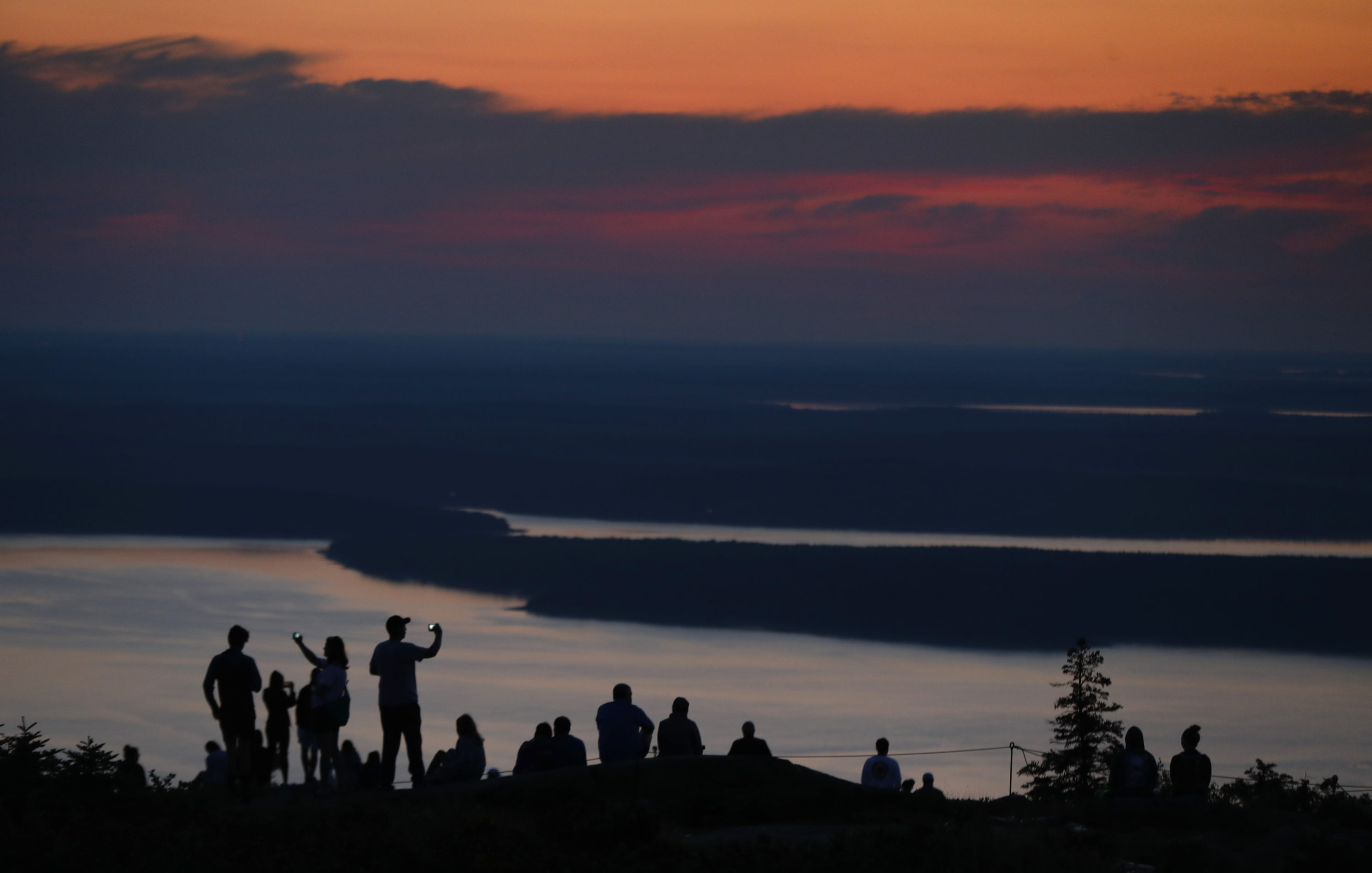 In this 2018 file photo, visitors to Acadia National Park enjoy an early sunrise near Bar Harbor, Maine. (Robert F. Bukaty/AP)