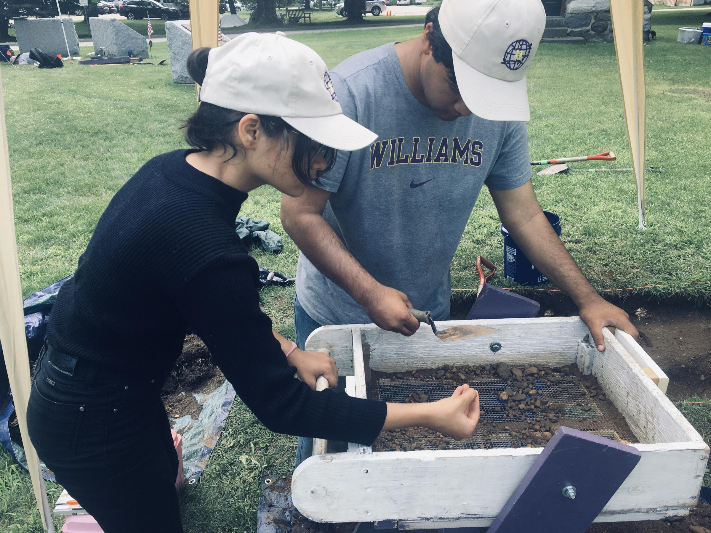 Williams College students Devika Goel and Hikaru Hayakawa work on the archaeological dig in Stockbridge, Massachusetts, organized by the Stockbridge-Munsee Band of Mohican Indians. (Nancy Eve Cohen/NEPM)