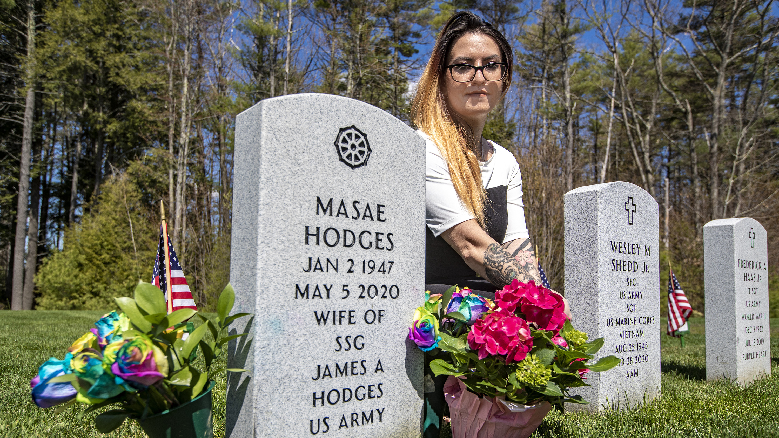 Suzanna Smith kneeling at the gravestone of her mother, Masae Hodges, at the Massachusetts Veterans' Memorial Cemetery in Winchendon. (Jesse Costa/WBUR)