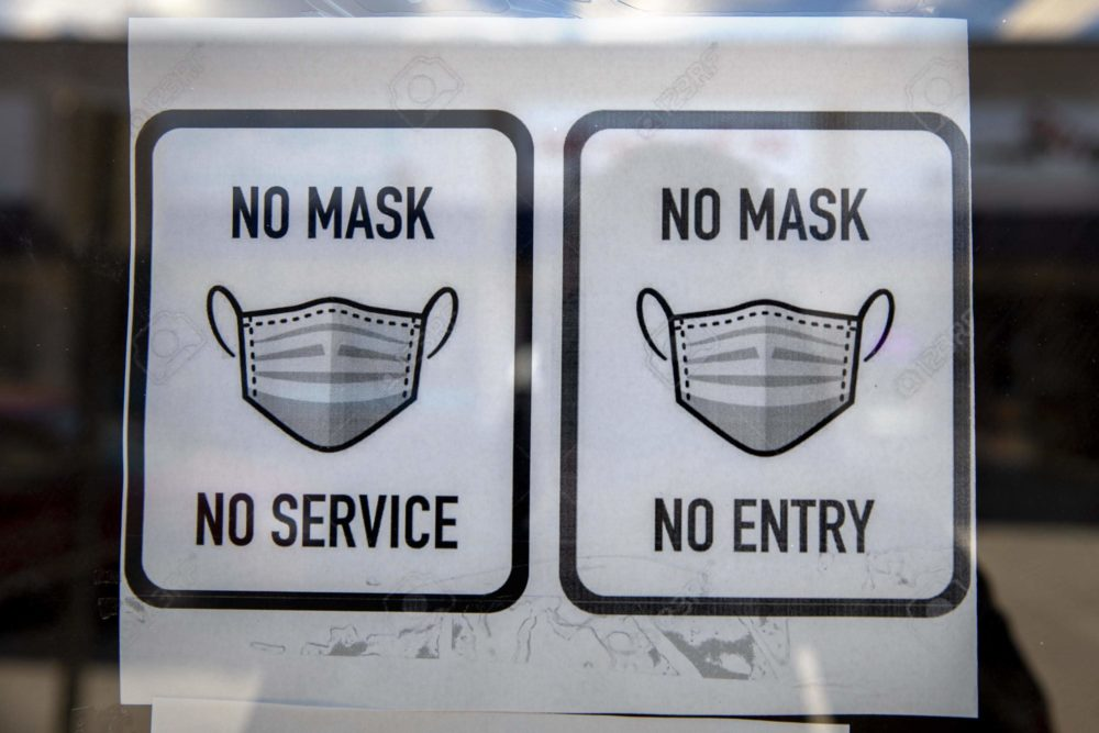 A sign requiring customers to wear masks is displayed on the door at Cash Point in Medford Square. (Robin Lubbock/WBUR)