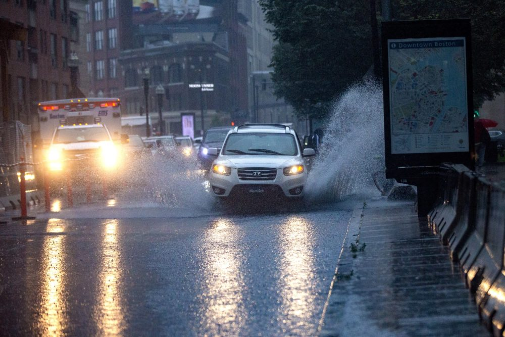 Cars drive through a flooded Stuart Street during the heavy rain from Tropical Storm Elsa on July 9, 2021. (Jesse Costa/WBUR)