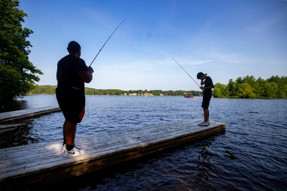 Chaun'cee Smith and Josiah Lopez fish off a dock in Lake Lashaway at Camp Atwater in North Brookville. (Jesse Costa/WBUR)