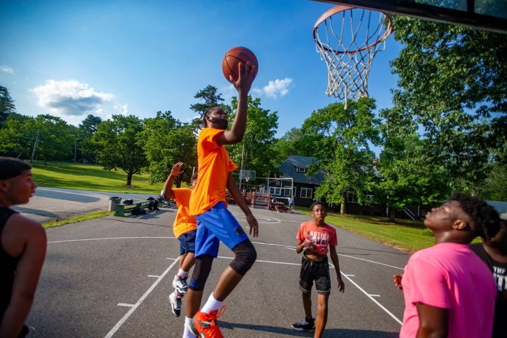 Joshua-Mark Campbell, 17, goes up for a layup while playing basketball with other boys at Camp Atwater. (Jesse Costa/WBUR)