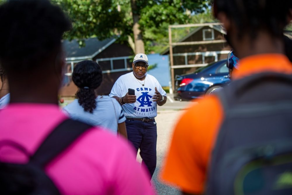After campers arrive from Springfield by bus, Urban League of Springfield President Henry Thomas III gives the words of encouragement to do anything they wish and to enjoy themselves while they are at Camp Atwater. (Jesse Costa/WBUR)