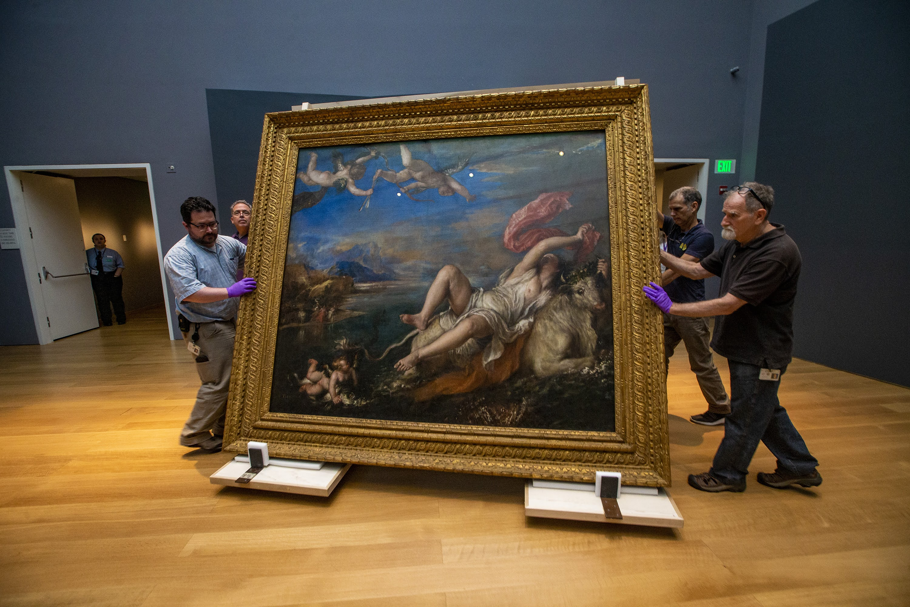 """Installers move Titian's """"The Rape of Europa"""" across the Hostetter Gallery after its return to the Isabella Stewart Gardner Museum from being on loan to the Prado Museum in Madrid, Spain. (Jesse Costa/WBUR)"""