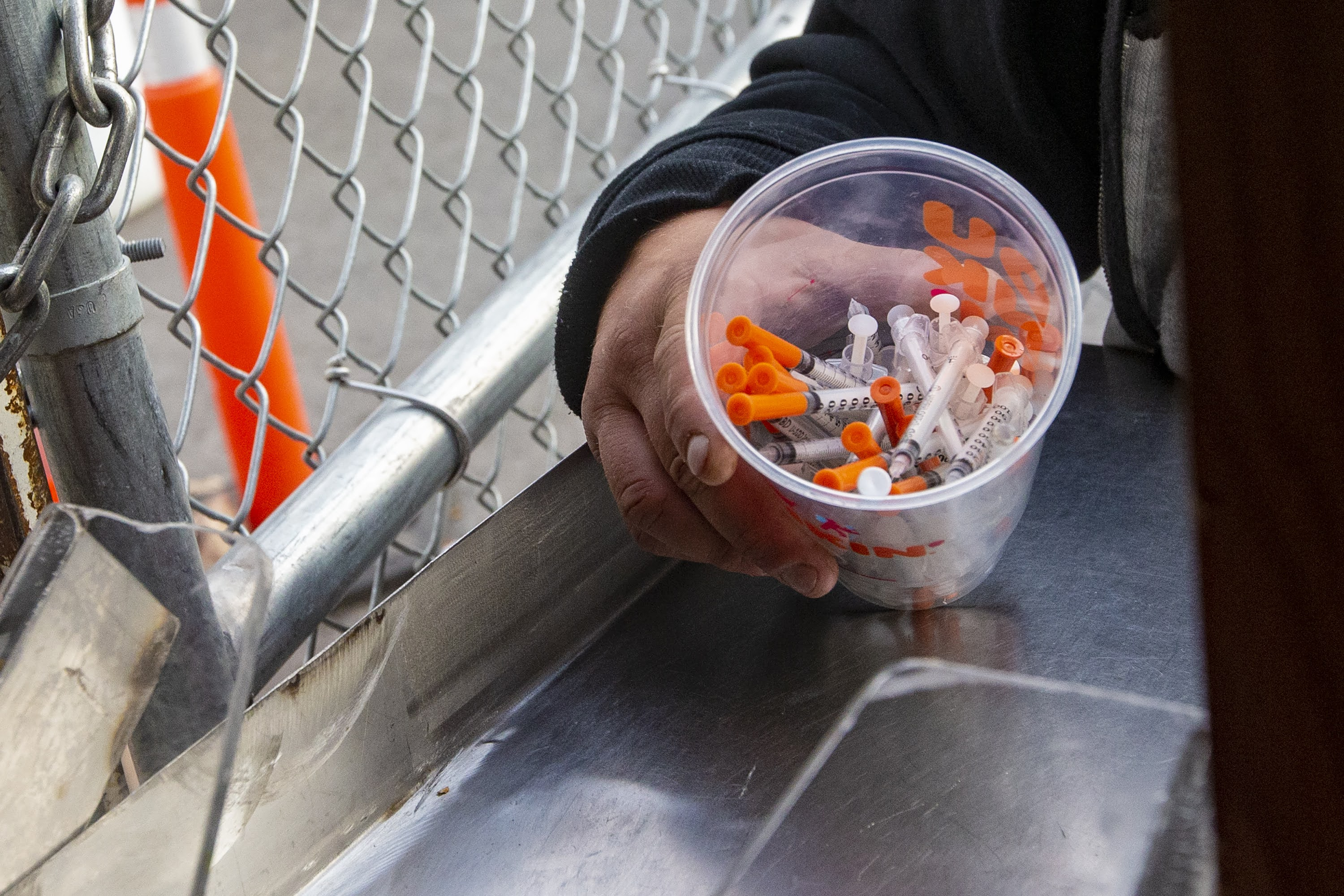 A man prepares to dump out a cup full of syringes at onto the counter as part of a syringe buy-back project in Boston run by the Community Syringe Redemption Program. (Jesse Costa/WBUR)