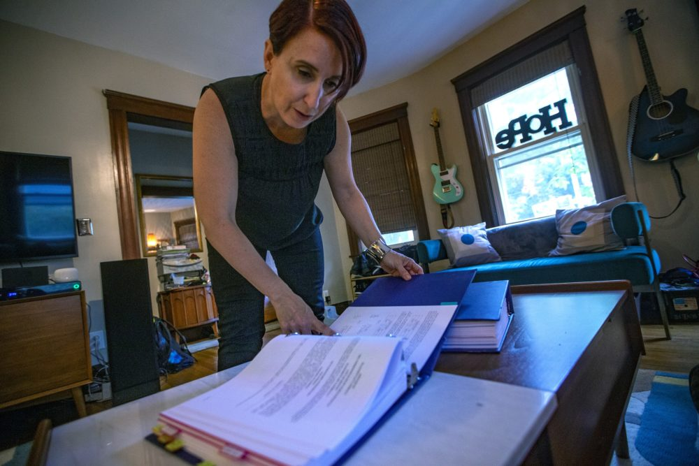 Kristin Johnson, a parent-advocate for a return to an elected school committee in Boston, leafs through binders full of documants she has collected about the history of the Boston School Committee. (Jesse Costa/WBUR)