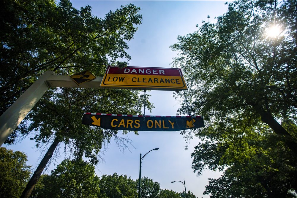 """A hanging """"Cars Only"""" sign on University Road warning drivers of the low clearence on Storrow Drive. (Jesse Costa/WBUR)"""