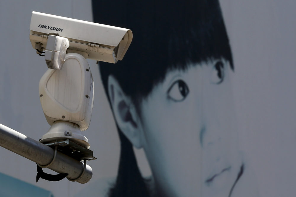 A video surveillance camera made by China's Hikvision is mounted on top of a street near a advertisement poster in Beijing, Thursday, May 23, 2019. (Andy Wong/AP)