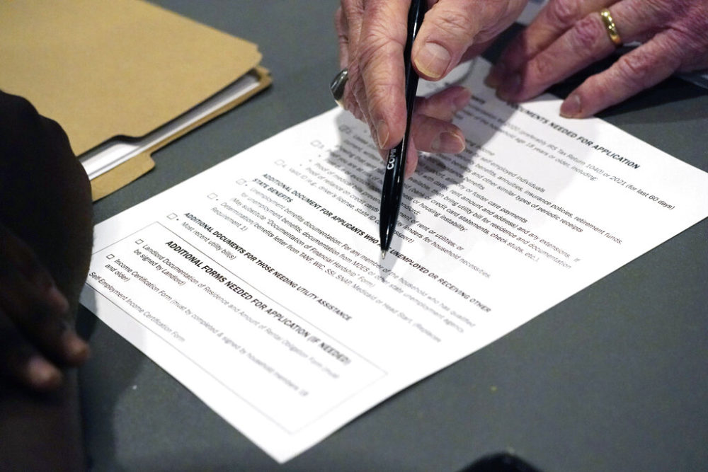 An applicant, left, is assisted by a volunteer with filling out the paperwork needed at a rental assistance fair. (AP Photo/Rogelio V. Solis)