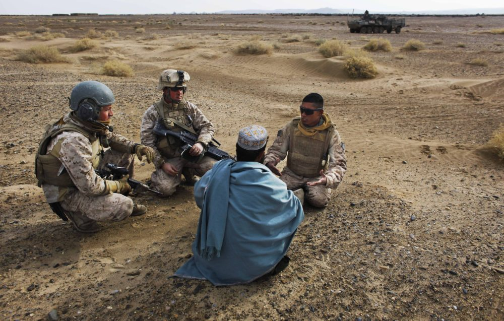 Dec. 11, 2009: United States Marine Sgt. Isaac Tate (left) and Cpl. Aleksander Aleksandrov (center) interview a local Afghan man with the help of a translator from the 2nd MEB, 4th Light Armored Reconnaissance Battalion on a patrol in the volatile Helmand province of southern Afghanistan. (Kevin Frayer/AP/File)