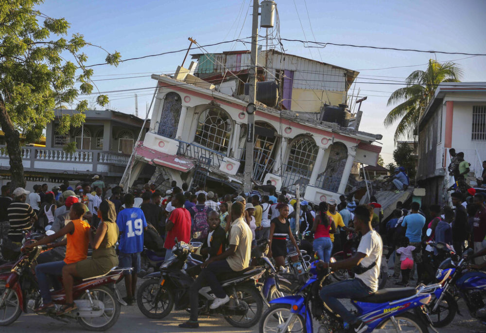 People gather outside the Petit Pas Hotel, destroyed by the earthquake in Les Cayes, Haiti, Saturday. (Joseph Odelyn/AP)