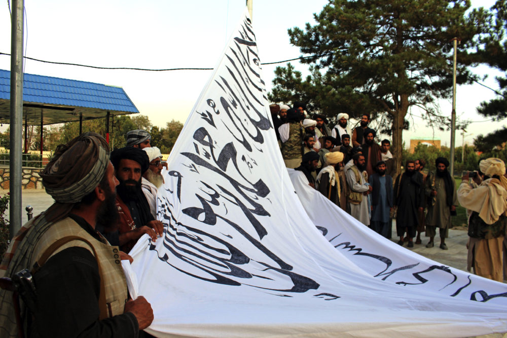 Taliban fighters raise their flag at the Ghazni provincial governor's house, in Ghazni, southeastern, Afghanistan, Sunday, Aug. 15, 2021. (Gulabuddin Amiri/AP)