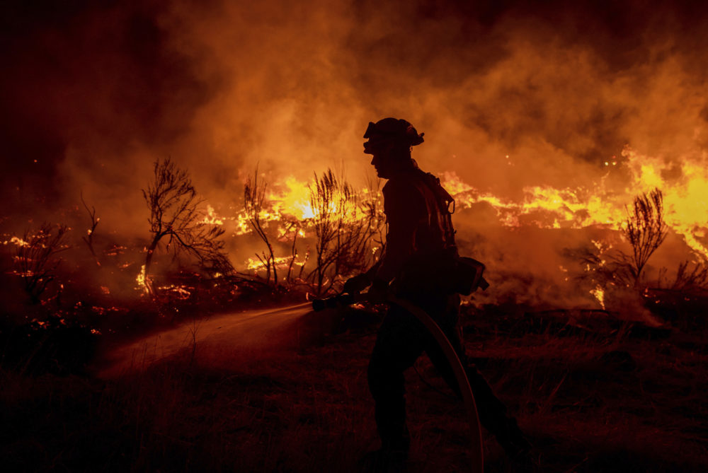 A firefighter hoses down areas of the Dixie Fire as it jumps Highway 395 south of Janesville, Calif., on Monday, Aug. 16, 2021. (Ethan Swope/AP)