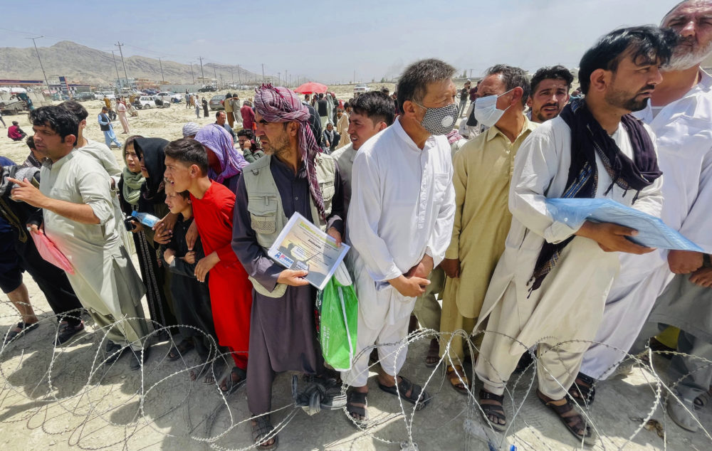 A man holds a certificate acknowledging his work for Americans as hundreds of people gather outside the international airport in Kabul, Afghanistan, Aug. 17, 2021. Deadly chaos gripped the main airport as desperate crowds tried to flee the country. (AP Photo)