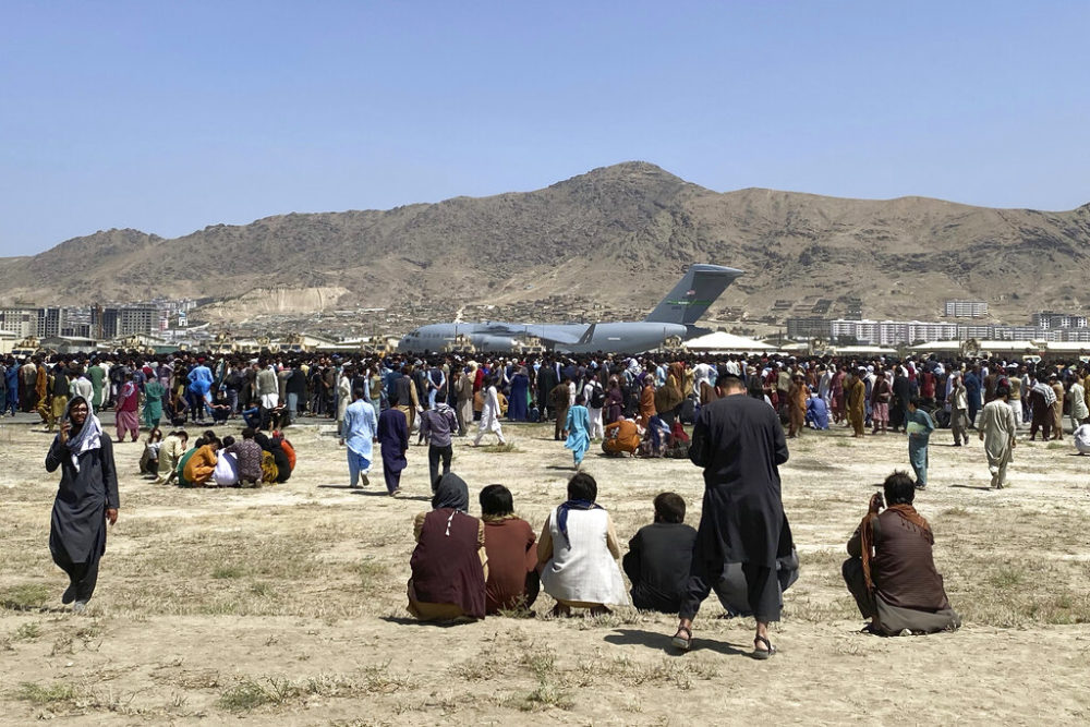 Hundreds of people gather near a U.S. Air Force C-17 transport plane at the perimeter of the international airport in Kabul, Afghanistan, Monday, Aug. 16, 2021. On Monday, the U.S. military and officials focus was on Kabul's airport, where thousands of Afghans trapped by the sudden Taliban takeover rushed the tarmac and clung to U.S. military planes deployed to fly out staffers of the U.S. Embassy, which shut down Sunday, and others. (Shekib Rahmani/AP)