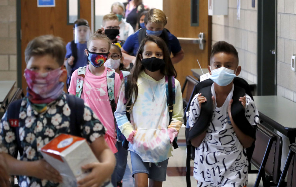 Elementary school students walking between classes are seen waring masks. (LM Otero/AP)