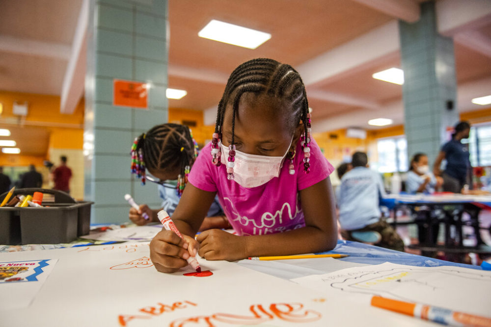 Liliana Lambert, 6, writes down and draws positive affirmations on poster board at P.S. 5 Port Morris, a Bronx elementary school, Tues., Aug. 17, 2021 in New York. (Brittainy Newman/AP)