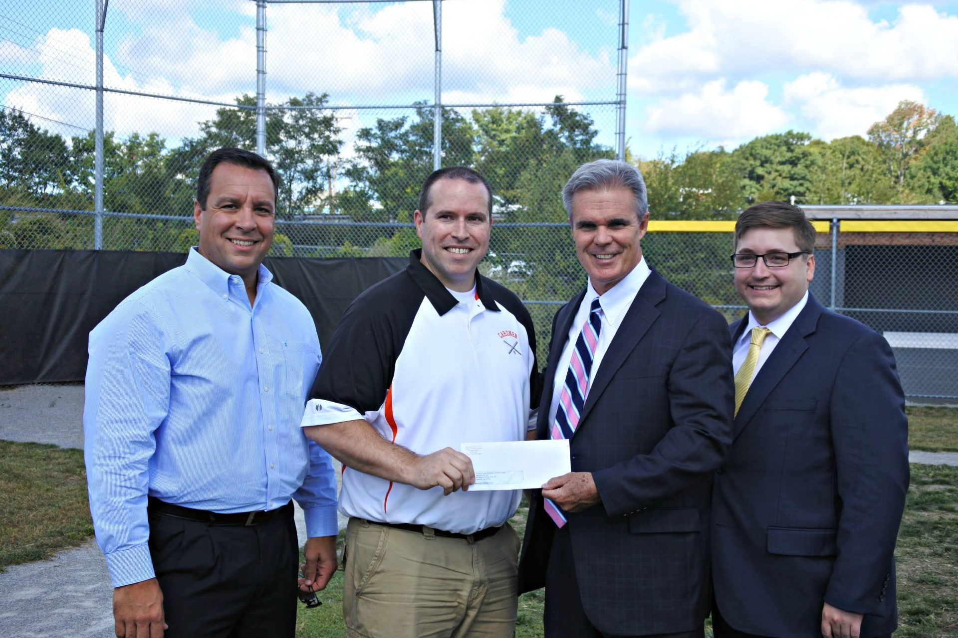 District Attorney Joseph D. Early Jr. presents a check from his county's drug forfeiture funds to Gardner Youth Baseball & Softball League to help improve their field. The league's president, Kevin Robillard, accepted the check and they were joined by former Gardner Mayor Mark Hawke and state Rep. Jonathan Zlotnik. (Photo published on Worcester County District Attorney's Office website in 2016)