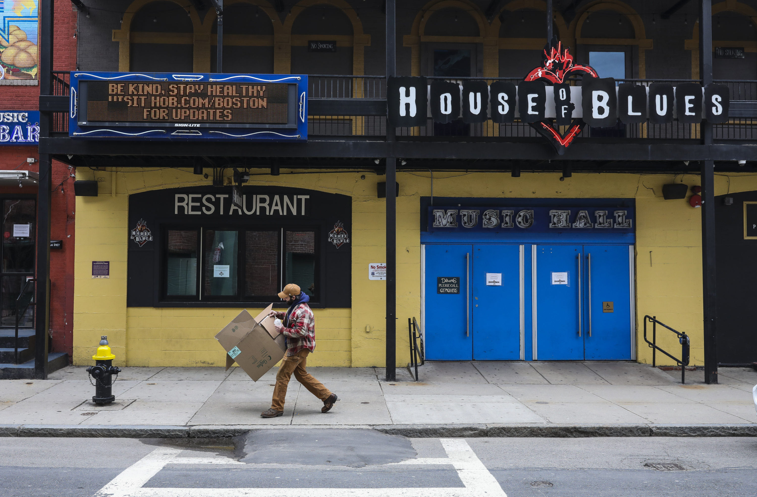 A man breaks down a cardboard box while walking past the House of Blues' COVID-19 sign urging people to be kind and stay healthy in April 2020. (Erin Clark/The Boston Globe via Getty Images)