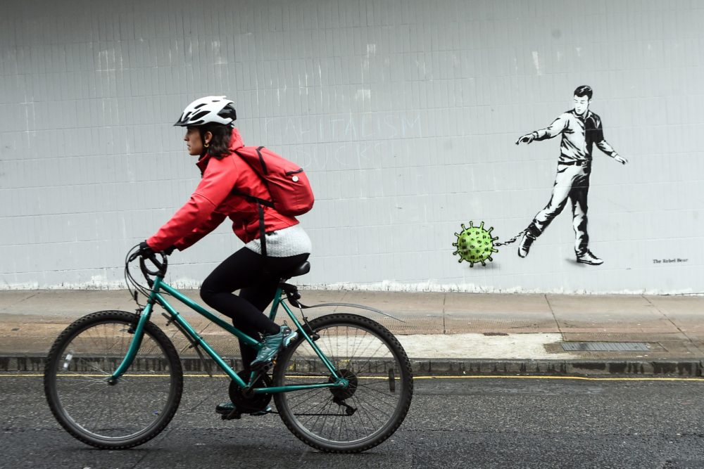 A cyclist passes a coronavirus-inspired piece of graffiti in Glasgow on April 4, 2020. (Andy Buchanan/AFP via Getty Images)