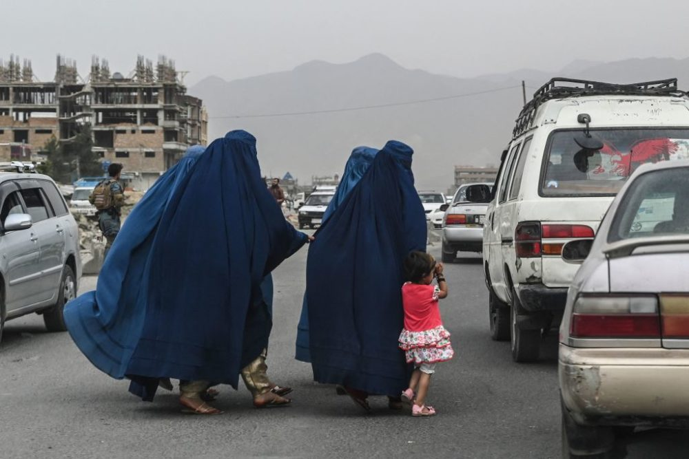 Women cross a road as they walk toward a local taxi in Kabul, Afghanistan, on July 31, 2021. (Sajjad Hussain/Getty Images)