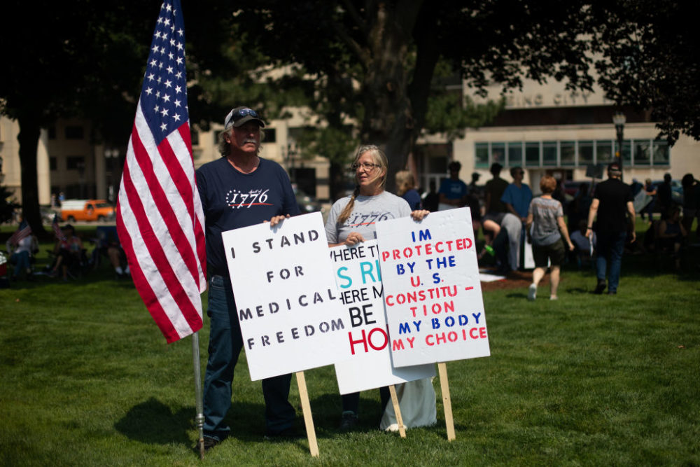 A couple holds sign as they join hundreds of other demonstrators gathering to protest against mandated vaccines outside of the Michigan State Capitol on August 6, 2021 in Lansing. There were 44 counties in Michigan at high or substantial levels of community coronavirus transmission, according to the CDC as of August 5, 2021. (Emily Elconin/Getty Images)