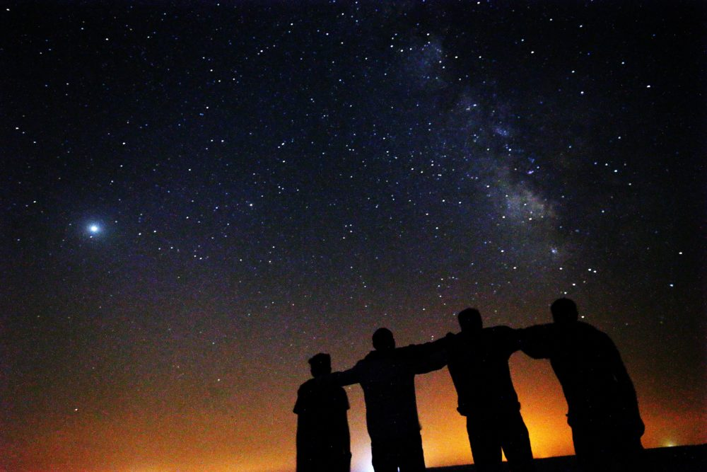 Friends look at the Milky Way galaxy rising in the night sky in Kuwait's al-Salmi desert, 120Km north of the capital, on Aug. 9, 2021. (Yasser al-Zayyat/AFP via Getty Images)