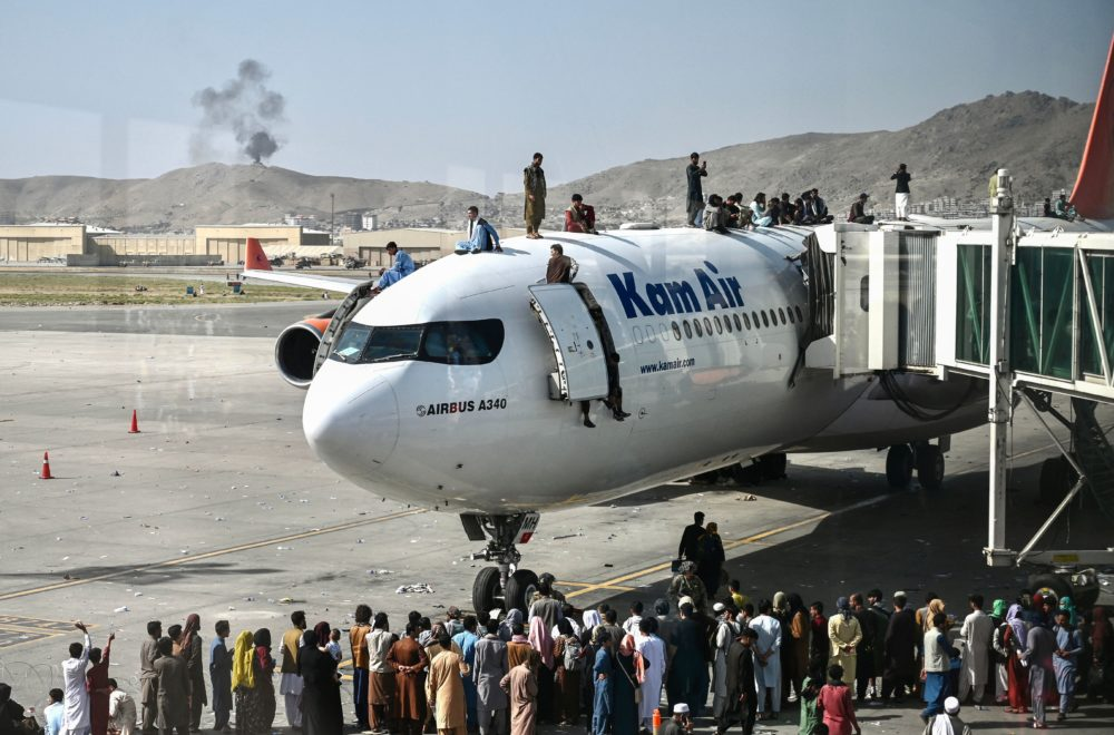 Afghan people climb atop a plane as they wait at the Kabul airport in Kabul on Aug. 16, 2021. (Wakil Kohsar/AFP via Getty Images)