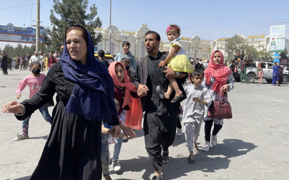 An Afghan family rushes to the Hamid Karzai International Airport as they flee the Afghan capital of Kabul, Afghanistan, on August 16, 2021. (Haroon Sabawoon/Anadolu Agency via Getty Images)