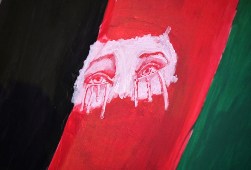 Tearful eyes are seen painted on a flag as members of the Los Angeles Afghan community and their supporters hold a vigil for Afghanistan outside the West LA Federal Building in Los Angeles, Aug. 17, 2021. (Robyn Beck/AFP/Getty Images)