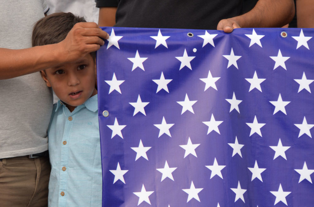 Afghan refugees, who fled Afghanistan in 1996, hold US flag as they attend a rally in front of the U.S. Embassy in Bishkek, on Aug. 19, 2021. (Vyachslav Oseledko/AFP/Getty Images)