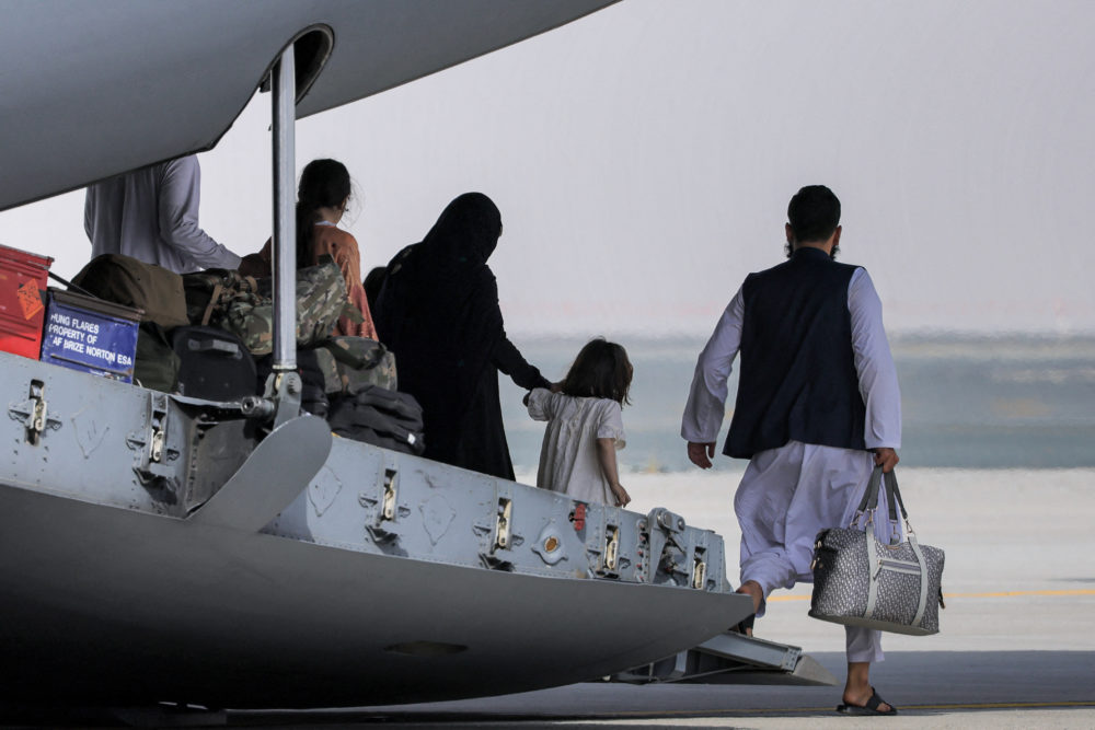 People disembark off a Royal Air Force military transport aircraft carrying evacuees from Afghanistan and arriving at Al-Maktoum International Airport in the United Arab Emirates on August 19, 2021. (Giuseppe Cacace/AFP via Getty Images)