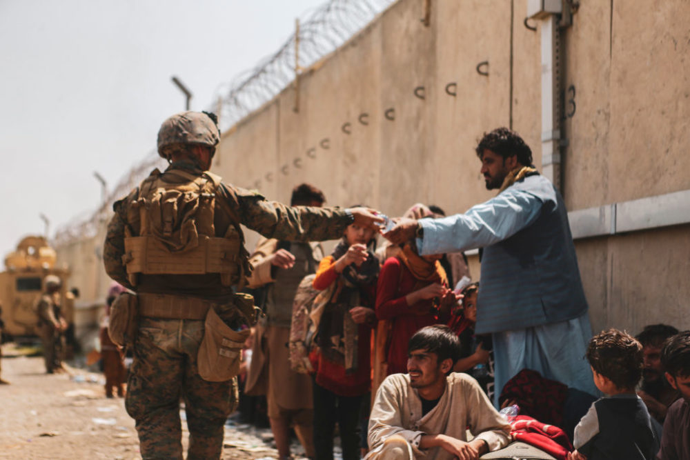 A marine with the 24th Marine Expeditionary unit (MEU) passes out water to evacuees during the evacuation at Hamid Karzai International Air. (Isaiah Campbell/U.S. Marine Corps via Getty Images)