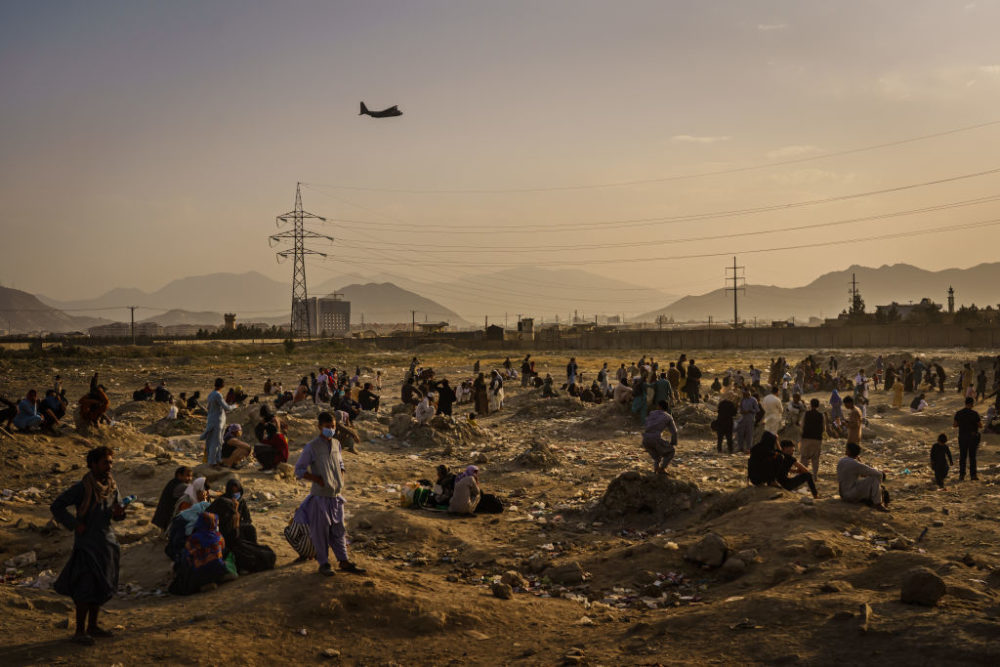 A military transport plane launches off while Afghans who cannot get into the airport to evacuate, watch and wonder while stranded outside, in Kabul, Afghanistan. (Marcus Yam / Los Angeles Times via Getty Images)